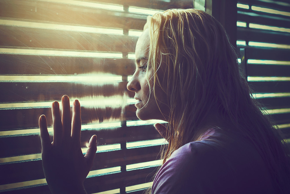 Young female, sad and lonely. Looking out window.