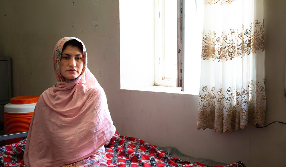 Brishna sits on a bed at a detention center in Kabul, where she is serving a 18 year sentence.