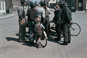 To tyske politifolk og en tysk pilot snakker med danske frihedskæmpere, mens et par danske børn lytter med. Foto: Nationalmuseet