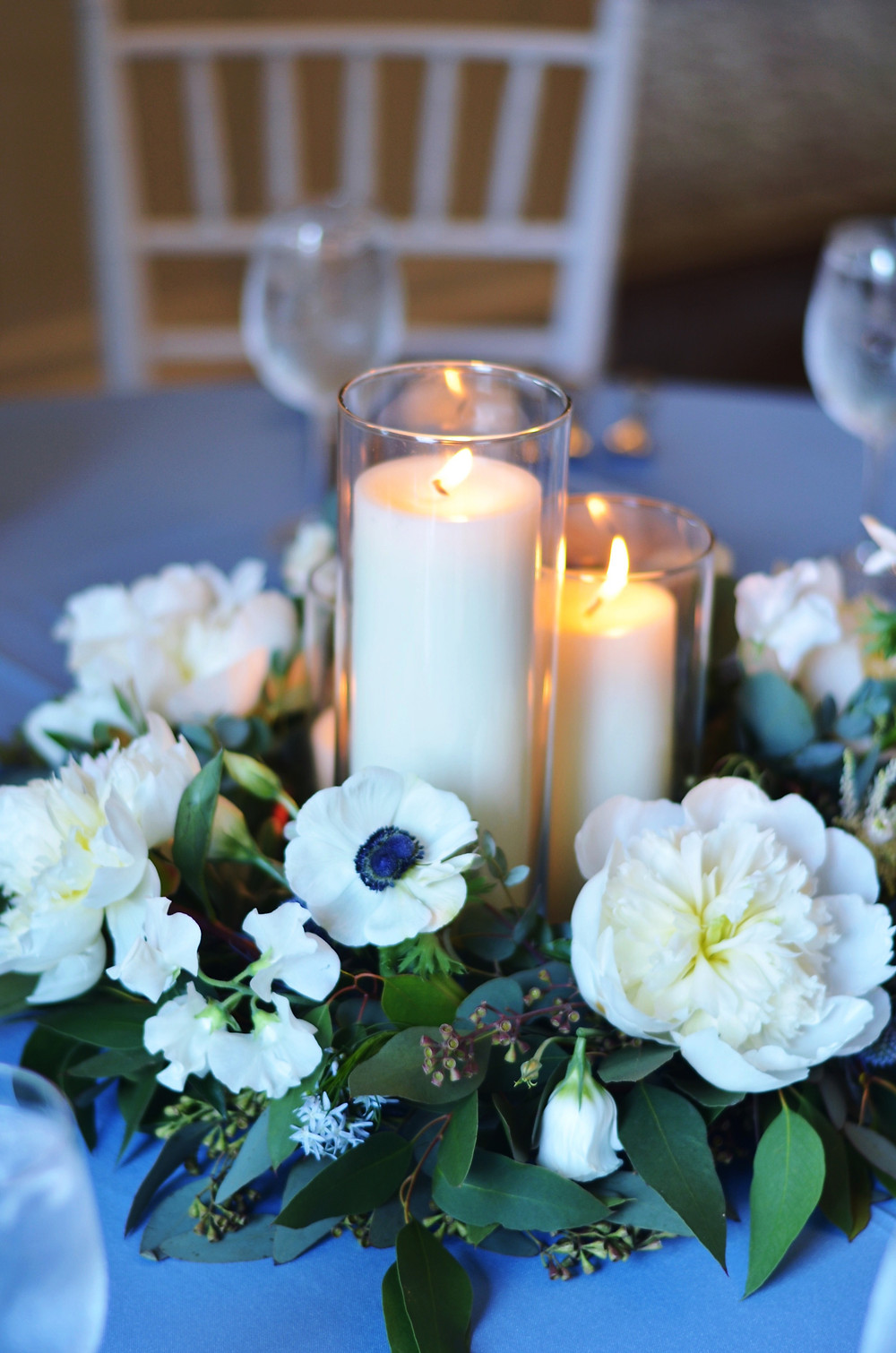 Low centerpieces with white Peony and pillar candles at Eolia Mansion, Harkness State
