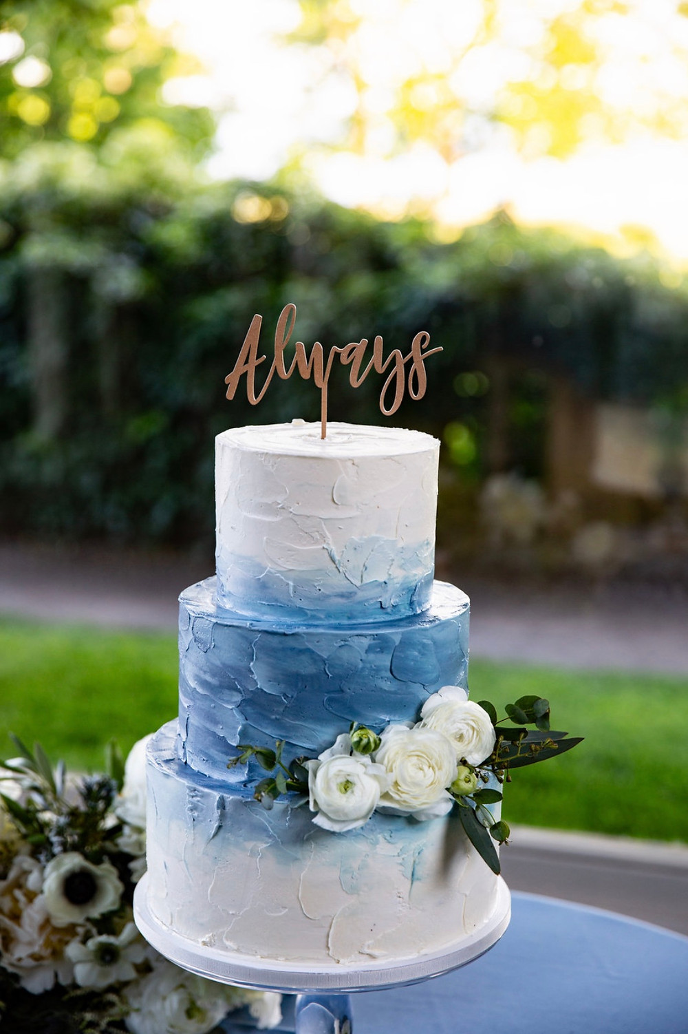 Dusty blue wedding cake with Ranunculus and Eucalyptus