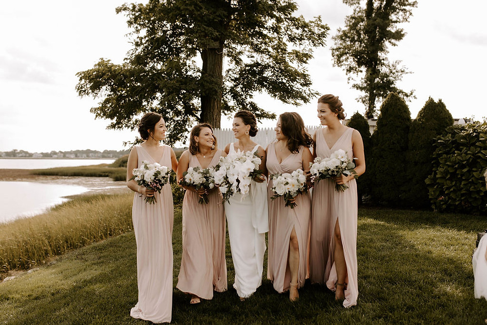 White cascading wedding bouquet and blush bridesmaid dresses