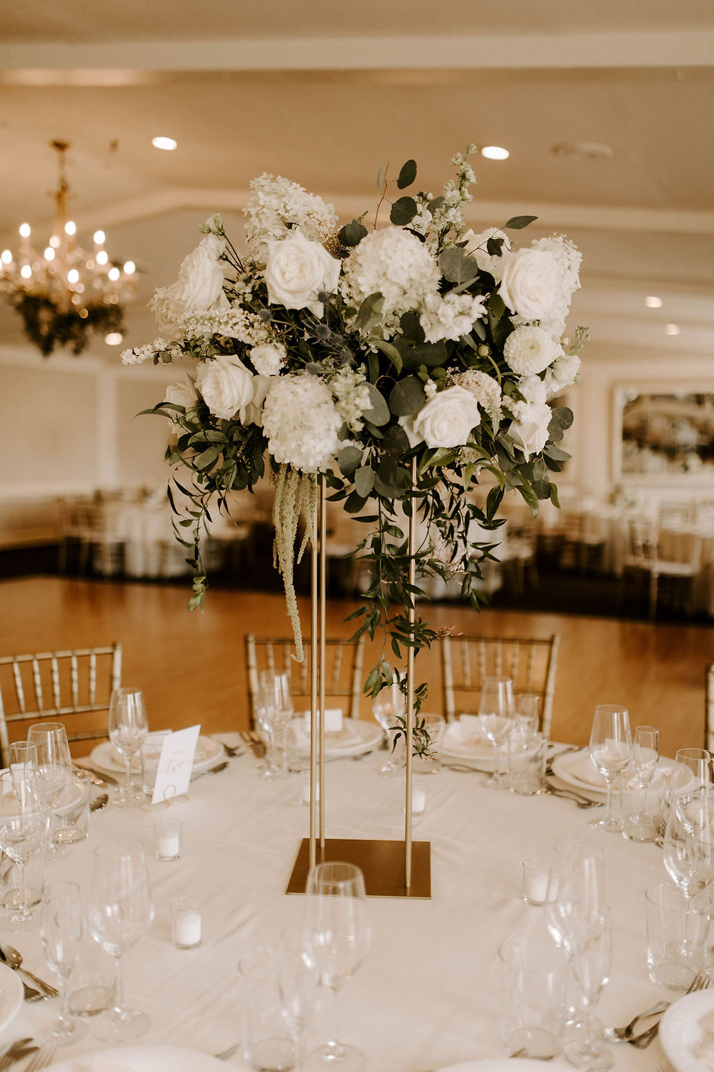 Tall centerpiece with white and greenery with natura style in gold stand at The Inn at Longshore