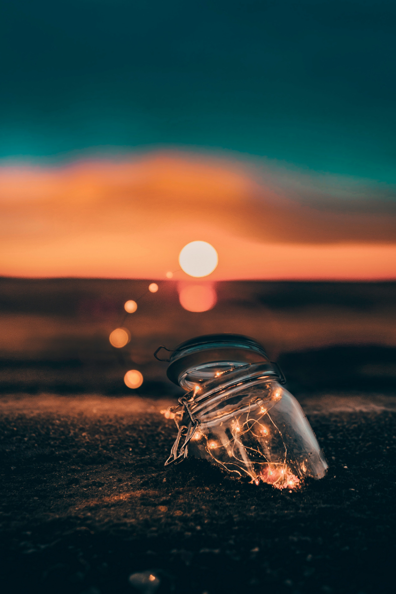 Photo of lights shimmering in glass bottle on the beach. Photo by Yeshi Kangrang