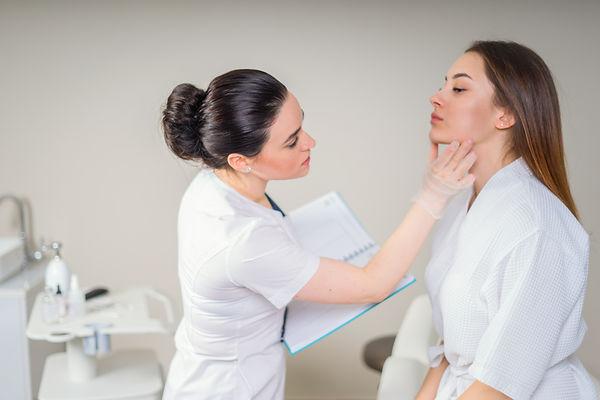 Professional cosmetician examining face