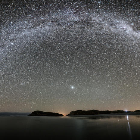 Wharariki Arch  A fully-overhead Milky Way arch, tracking 180° from Wharariki rocks (The now famous cow-and-calf, thanks Windows10!) to where a group of kids were fortuitously having a bonfire on the beach