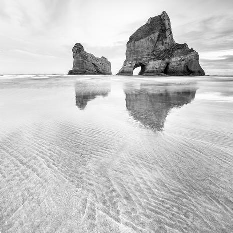 The Rocks and Sands.  Wharariki beach and the Archway islands reflected in the wet sands  BW005