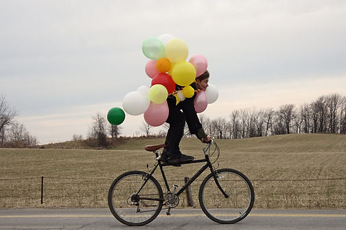 Man riding a bike and holding balloons