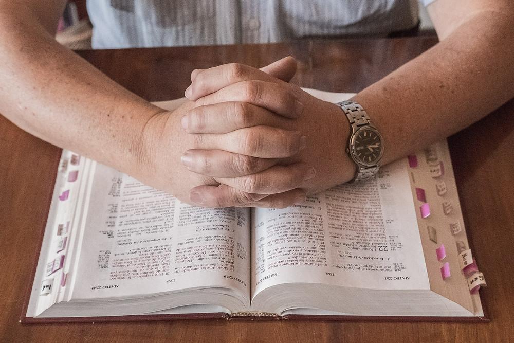 Dos manos unidas en símbolo de oración, encima de una Biblia en español.