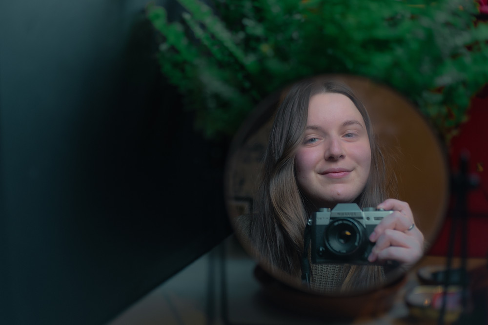 Kayleigh is taking an image with her new Fuji X-T30. She, and the camera, is framed in the reflection of a mirror, framed by a green fern plant.