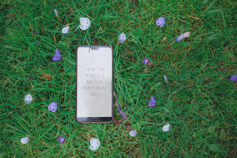 A flat-lay of a phone surrounded by purple and white Crocus flowers. The phone reas, 'How To Write A Killer Instagram Post'.