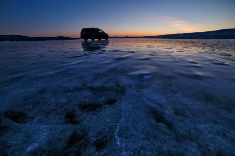 Машина фототура после заката на льду Байкала