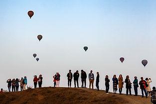 Туристы наблюдают за воздушными шарами в Каппадокии