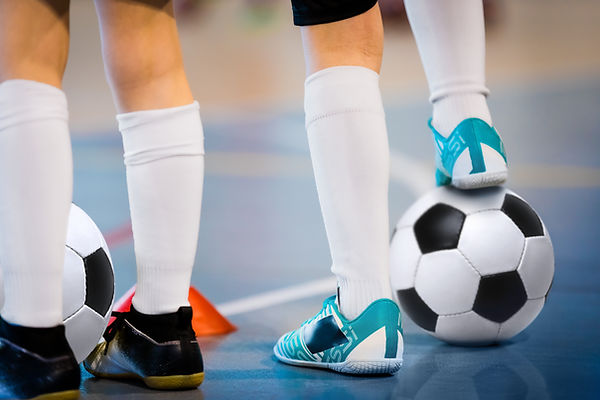 Indoor soccer players training with ball