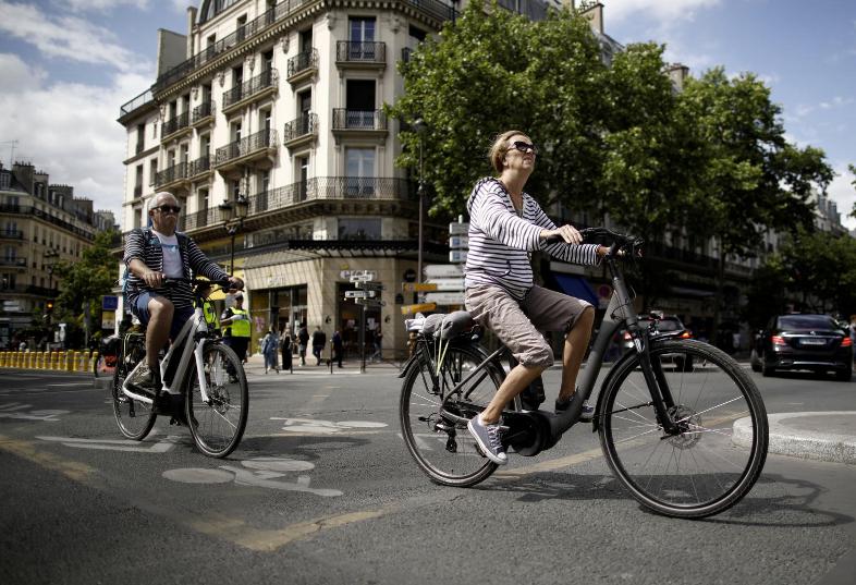 A woman riding a bike in Reuters. Photo Credit: REUTERS/Benoit Tessier/File