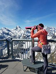 woman looking through binoculars at mountains swiss alps