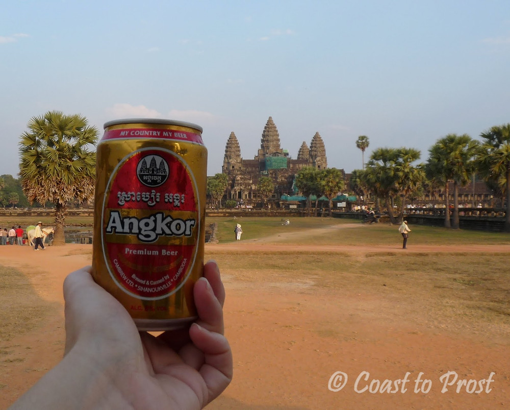 holding an Angkor beer can in front of the main temple