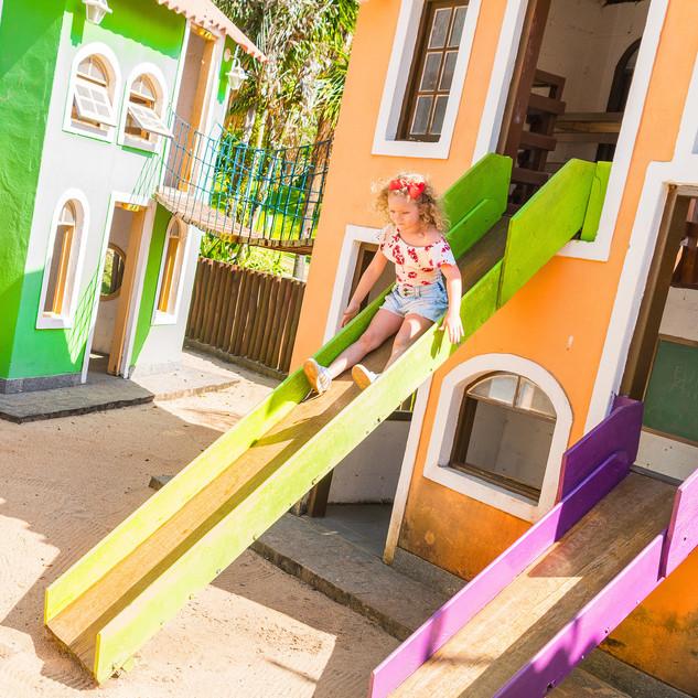 menina brincando no escorregador casinha