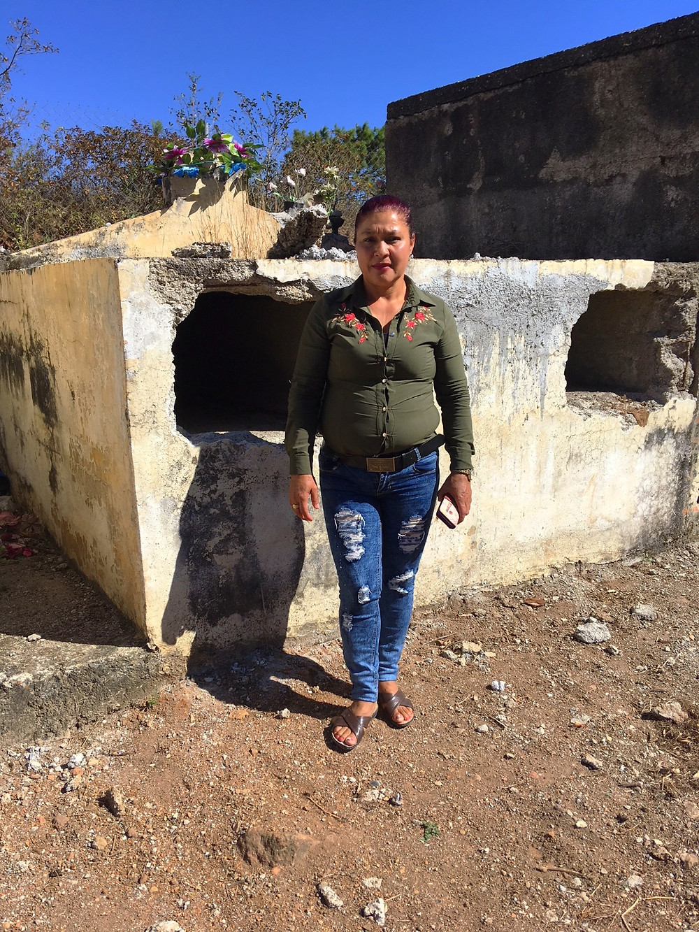 Miriam Varga stands in front of the grave that was broke open to remove her husband without her permission.