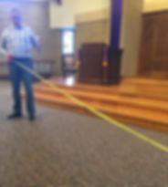 Chapel Time with Pastor Erik. He can be seen in front of th pulpit and stairs leading up to it holding one end of a tape measure. The other end is off screen