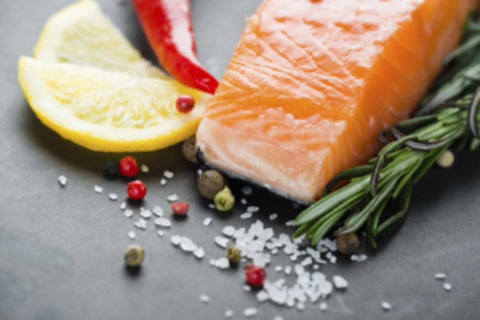 fresh portion of salmon alongside herbs, sliced lemon, a dash of cracked pepercorn and seasalt