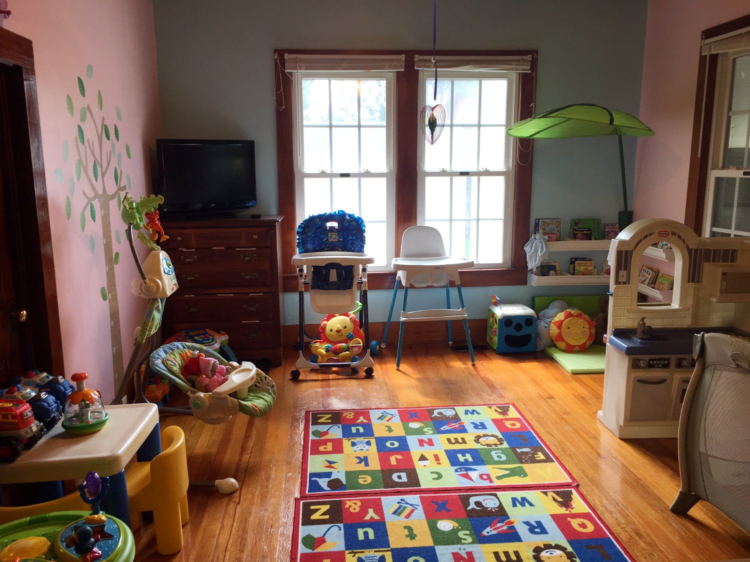 The infant room has been updated with new flooring, blue and pink walls, and a reading corner.
