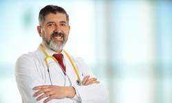 Mature doctor smiling with large window in background_edited