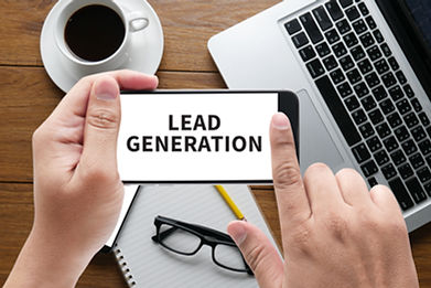 LEAD GENERATION message on hand holding to touch a phone, top view, table computer coffee