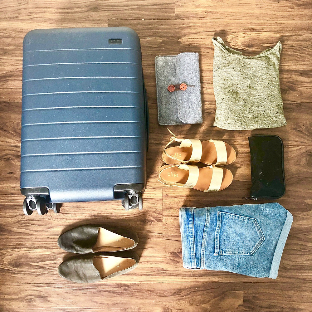 Some of my packing essentials - my Away bag, comfy shoes, iPad, chargers, and neutral-colored clothing.