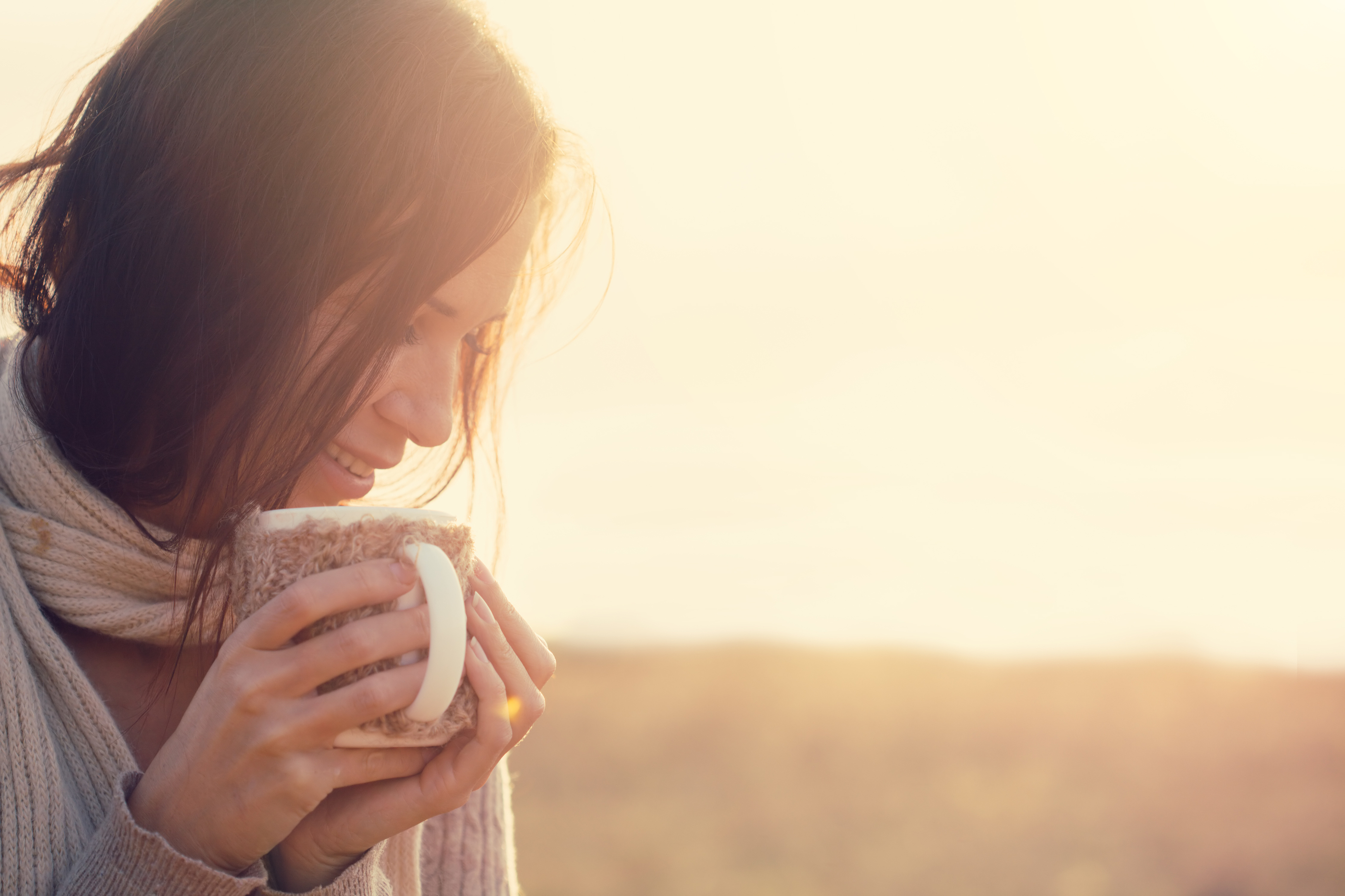 Woman wearing warm knit clothes drinking cup of hot tea or coffee outdoors in su