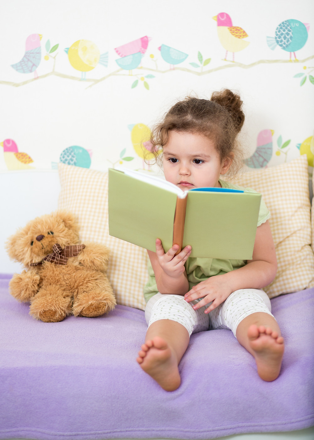 little girl holding a book while sitting on a purple cushion