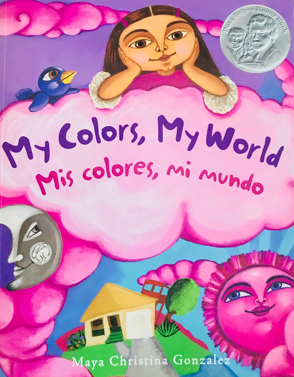 Book cover of My Colors My World. Little girl resting her elbows on a fluffy cloud looking down to her neighborhood. The sun and moon are looking up at her.