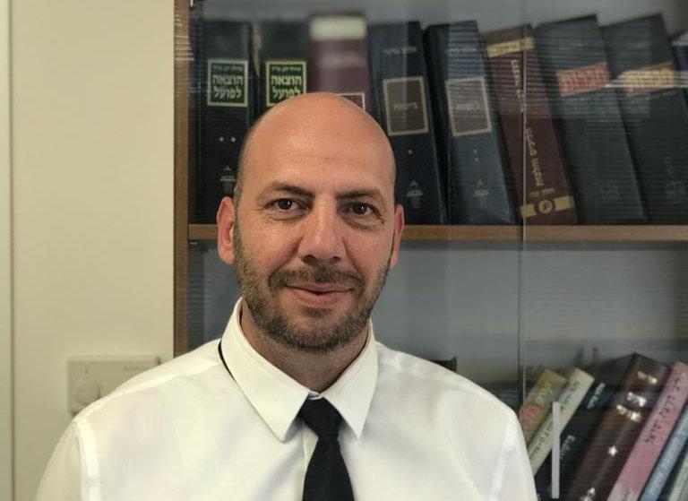 עורך הדין אהוד גרבר במשרד. ברקע סיפ סיפריית המשרד