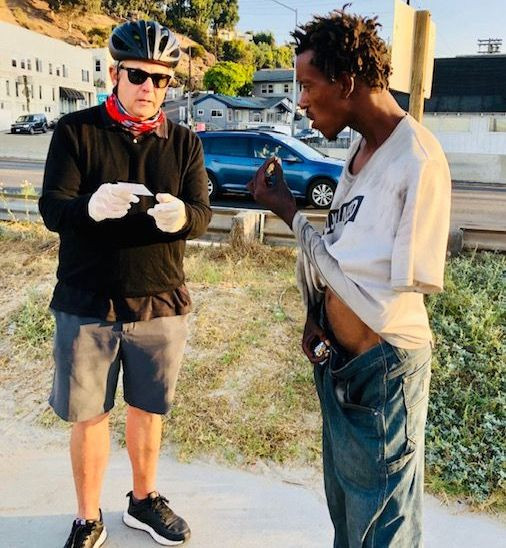 Gregg Seltzer engaging a new homeless individual with service information card