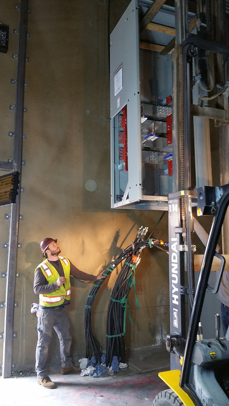 While wearing the appropriate personal protective equipment, our team of Diversified Electricians installing a new electrical panel into position.