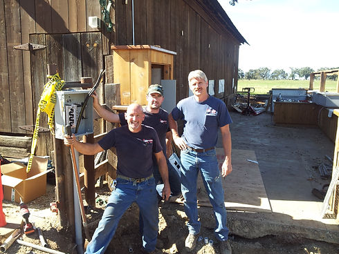 A group of electricians working on a sub panel in Mount Shasta all wearing DES shirts.