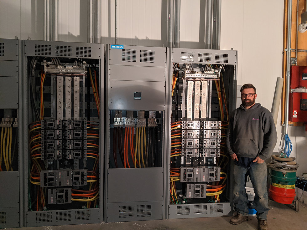 John is standing in front of a set of beautifully wired large electrical panels. The excellent wiring job done by the Diversified Electric, Inc. team of electricians is mesmerizing to look at.