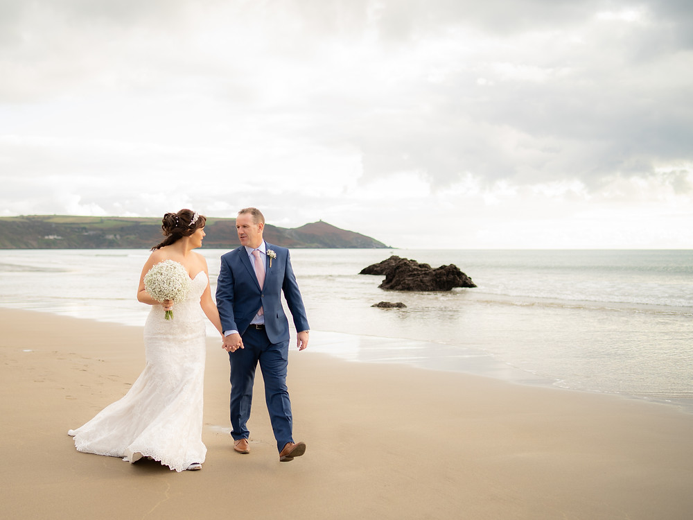 Bride & Groom taking a stroll along the beach at Whitsand Bay