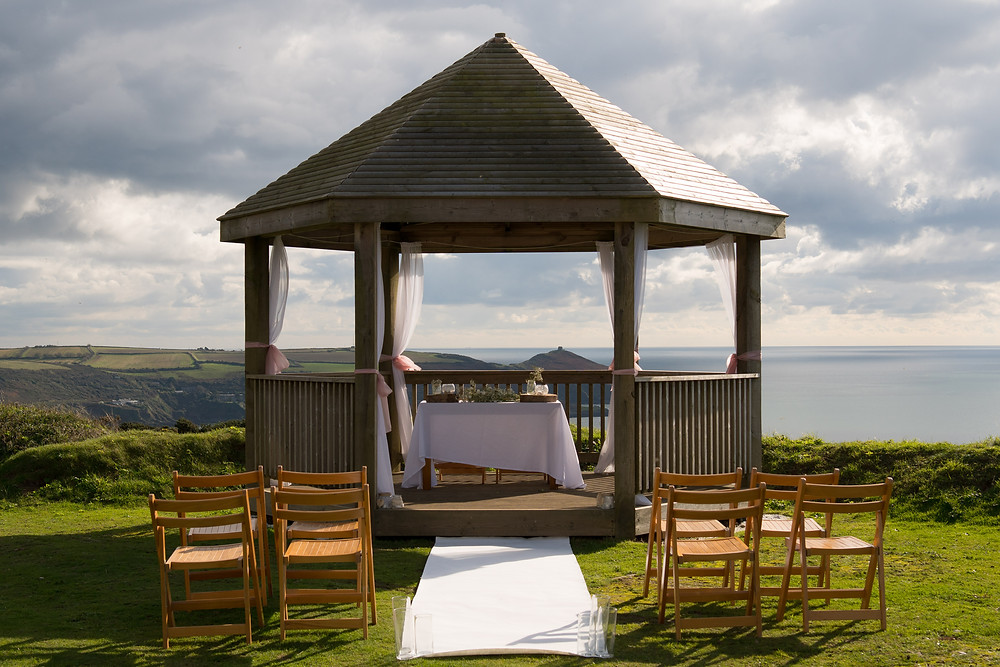 Clifftop wooden arbor decorated for a small wedding at Whitsand Bay
