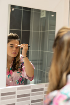Girl applying makeup in the mirror