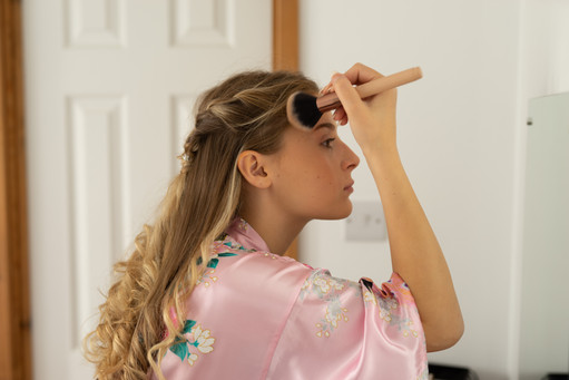 Bridesmaid applying makeup in the mirror