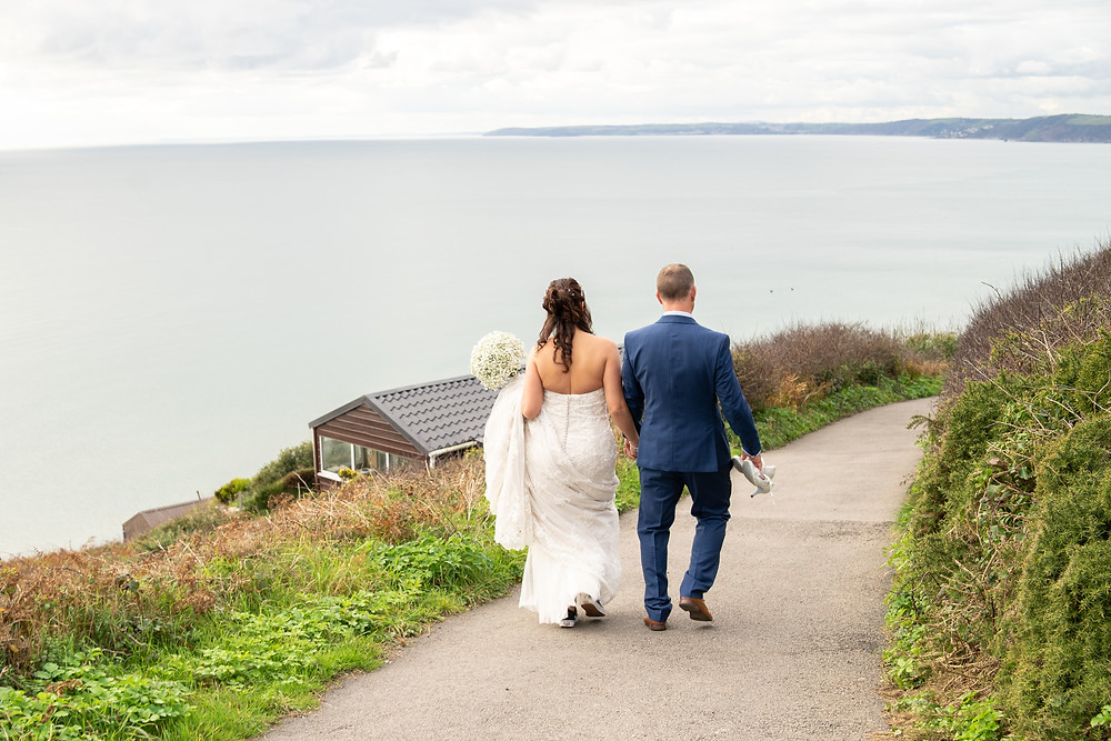Bride & Groom walking down a coastal path to the beach at Whitsand Bay