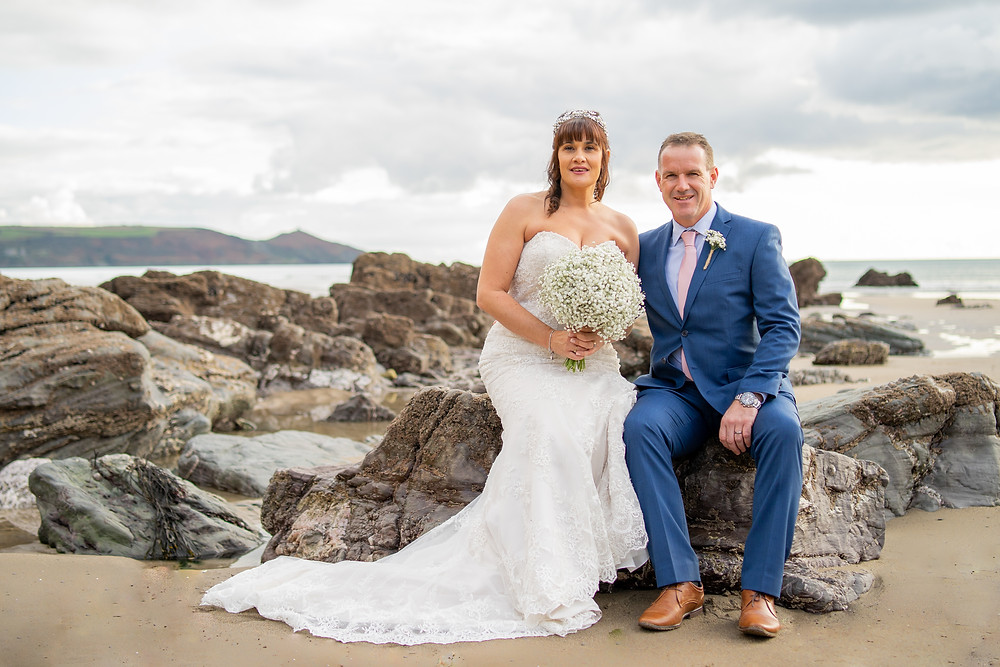 Bride & Groom sitting on a rock on the beach at Whitsand Bay
