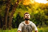 A bearded man is meditating on green gra