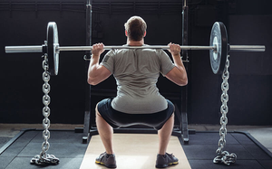 Back view of a man squatting with a barbell w/ weights and chains on each side