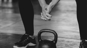 Imagine of a fit woman squatting over a kettlebell, with chalk on her hands.