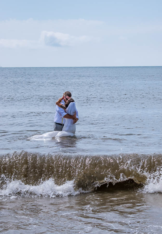 bride and groom in water at beach elopement