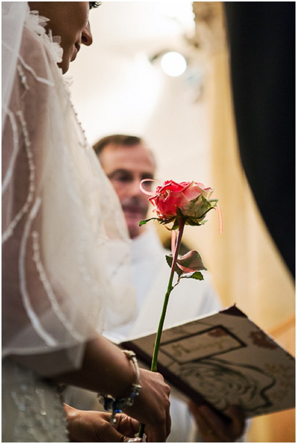 bride with single rose to exchange with groom during wedding ceremony