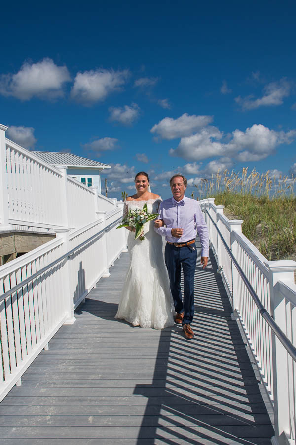 father and bride walking boardwalk to beach wedding folly beach sc