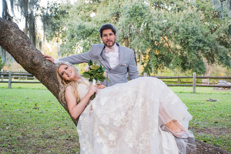 bride laying in a tree with groom standing over her